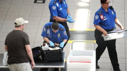A Transportation Security Administration(TSA) agent checks the luggage of a passenger(L) (AFP Photo / Stan Honda)