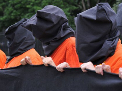 Anti torture activists dressed in the orange jumpsuits and black hoods that are now emblematic of the policies of torture and abuse that the Obama administration (AFP Photo / Karen Bleier)