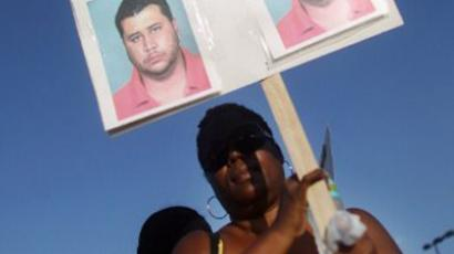 A protester holds a sign with pictures of George Zimmerman at a rally for slain teenager Trayvon Martin on March 22, 2012 in Sanford, Florida (Mario Tama/Getty Images/AFP)