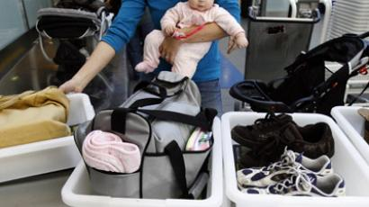 A passenger holding her baby prepares to go through an airport security checkpoint (Reuters / Mario Anzuoni)