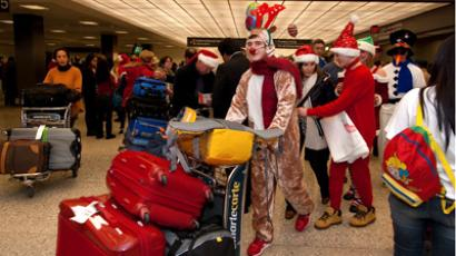 A dressed up family member pushes a relative's luggage in the international arrivals area of at Dulles International Airport (IAD) on their way to celebrate Christmas. (AFP Photo / Paul J.Richards)