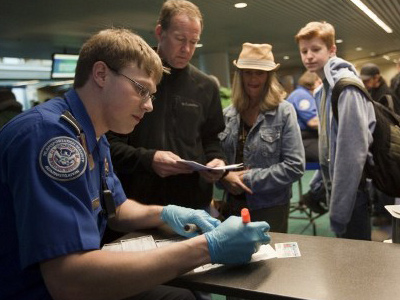 Passengers line up to a Transportation Security Administration (TSA) officer to go through airport security at Portland International Airport (Natalie Behring/Getty Images/AFP)