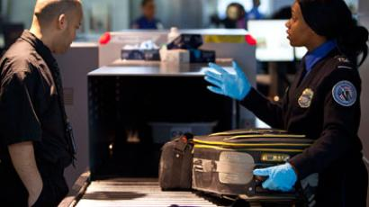 A Transportation Security Administration (TSA) security agent takes a traveler's luggage for a second security check at John F. Kennedy Airport in New York.(Reuters / Andrew Burton)