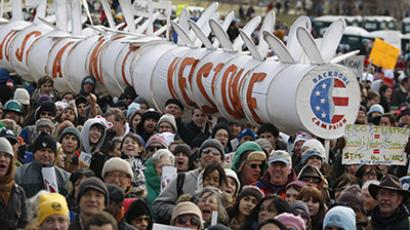 Demonstrators carry a replica of a pipeline during a march against the Keystone XL pipeline in Washington, February 17, 2013. (Reuters /  Richard Clement)