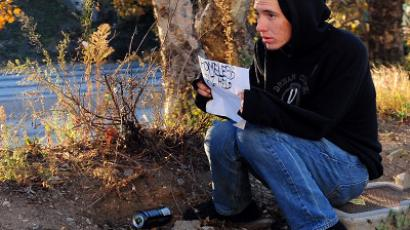 A young man sits beside a freeway off ramp holding a sign that reads 'Homeless Plz Help' (AFP Photo / Frederic J. Brown)