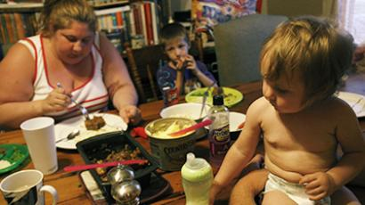 Katie Busker and her family eat dinner. Busker, who receives food stamps and is unemployed due to a disability, stays home and watches the kids. (Reuters /  Jessica Rinaldi)