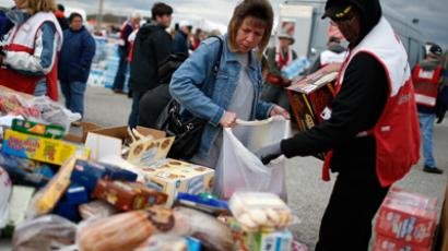 A victim of Hurricane Sandy is helped by a volunteer to load food in bags from a FEMA and American Red Cross aid and disaster relief station in the hard-hit Staten Island section of New York City November 2, 2012 (Reuters / Michael Loccisano)