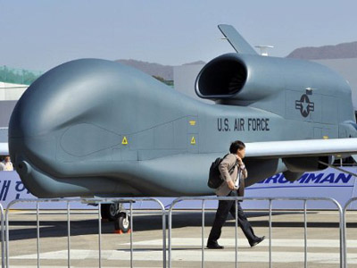 A man walks past a US Air Force Global Hawk unmanned aerial vehicle hanger during a preview day of the Seoul International Aerospace and Defense Exhibition at a military air base in Seongnam, south of Seoul, on October 17, 2011. (AFP Photo / JungYeon-Je)