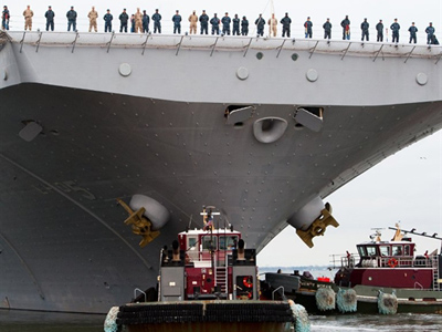 Crew members stand on the deck of the USS Bataan (rear) as tug boatS push her away from the dock to lead the Bataan Amphibious Ready Group out of the Norfolk, Virgina, US Naval Base, March 23, 2011, enroute to waters off Libya (AFP Photo / Paul J. Richards)