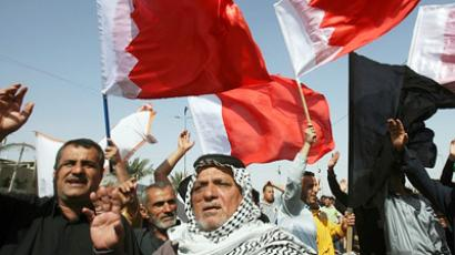 Iraqi Shiite Muslims hold up the Bahraini flag as they protest in Sadr City in eastern Baghdad on March 16, 2011