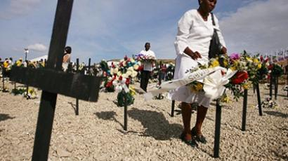 A woman places flowers on a cross at St. Christophe, where thousands of victims of the January 12, 2010 earthquake are buried, in Port-au-Prince on January 11, 2011 (AFP Photo / Hector Retamal)