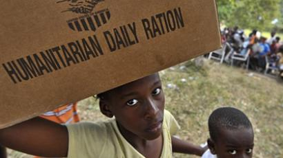 An Haitian child carries a box with food supplies at a refugee camp (AFP Photo / Luis Acosta)