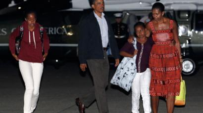 U.S. President Barack Obama (2nd L) and his family walk to board Air Force One after cutting short by a day their vacation on Martha's Vineyard in Massachusetts August 26, 2011 (Reuters / Kevin Lamarque)