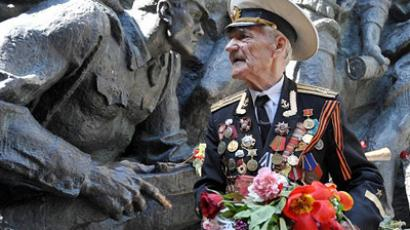 Ukraine, Kiev: A World War II veteran pays his respects at a momument commemorating victory in the war on Victory Day marking the anniversary of the end of WWII in Kiev on May 9, 2011. (AFP Photo / Genya Savilov)