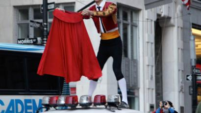 A man dressed as a matador fightswith the Wall Street Bull in Manhattan. Photo credit: Bess Adler.