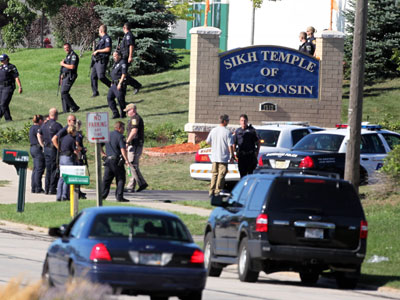 Oak Creek : Law enforcement personnel walk outside the Sikh Temple of Wisconsin where at least one gunman fired upon people at a service. (AFP Photo / Tasos Katopodis)