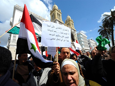 Tunisian protesters wave Libyan and Syrian flags as they take part in a demonstration in solidarity with the Libyan and Syrian people and opposition, in Tunis (AFP Photo / Fethi Belaid)