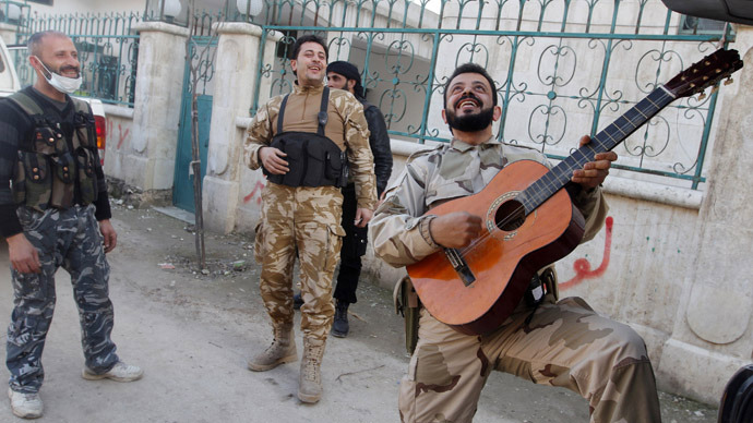 Members of the Free Syrian Army chant as one of them plays the guitar near Nairab military airport in Aleppo February 26, 2013. (Reuters/Hamid Khatib)
