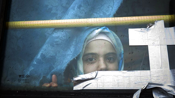 A Syrian girl looks through the window of a bus where she has lived with her family for the past eight months at a refugee camp in Bab al-Salam on the Syria-Turkey border. (AFP Photo / Bruno Gallardo)