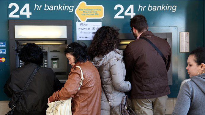 People withdraw money from a cash-point machine in the Cypriot capital Nicosia on March 17, 2013. (AFP Photo)