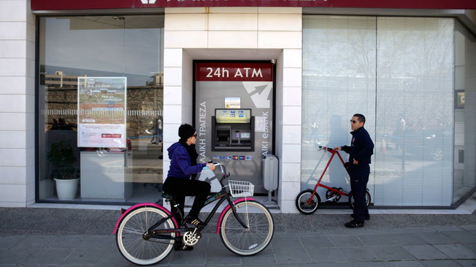 A woman rides her bike past a Laiki (Popular) Bank branch on March 25, 2013 in Nicosia.(AFP Photo / Yiannis Kourtoglou)