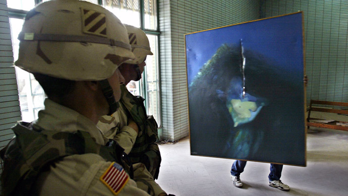 US soldiers look at a painting 24 April 2003 as workers at Baghdad's Archaeological Museum carry in some of the recovered items that had been looted following the US-led invasion to the Iraqi capital city. (AFP Photo)