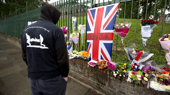A man looks at floral tributes left at the scene where Drummer Lee Rigby of the 2nd Battalion was killed outside Woolwich Barracks in London on May 24, 2013. (AFP Photo / Justin Tallis)