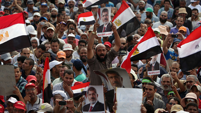 Supporters of deposed Egyptian president Mohamed Morsi hold portraits of him and national flags during a rally on July 9, 2013 outside Cairo's Rabaa al-Adawiya mosque (AFP Photo/Mahmud Hams)