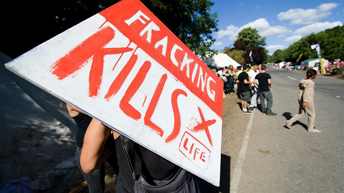 "A climate and anti-fracking protester holds a ""Fracking kills"" placard as he stands outside the test drill site operated by British energy firm Cuadrilla Resources in Balcombe, southern England, on August 20, 2013. (AFP Photo / Leon Neal)"