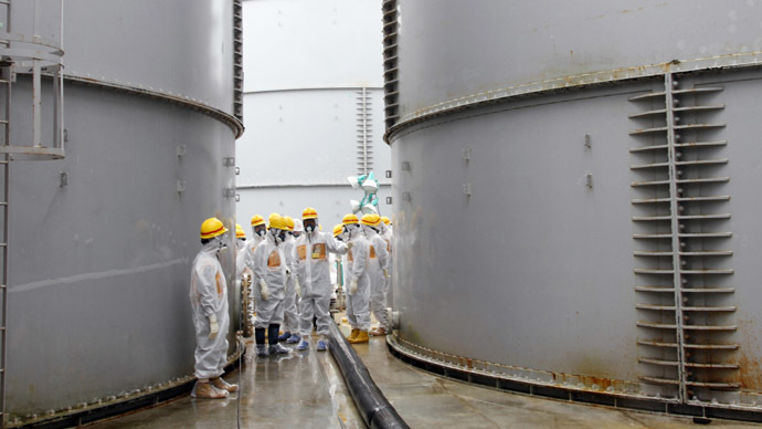 This handout picture taken by Japan's Nuclear Regulation Authority on August 23, 2013 shows nuclear watchdog members including Nuclear Regulation Authority members in radiation protection suits inspecting contaminated water tanks at the Tokyo Electric Power Co (TEPCO) Fukushima Dai-ichi nuclear power plant in the town of Okuma, Fukushima prefecture. (AFP Photo)