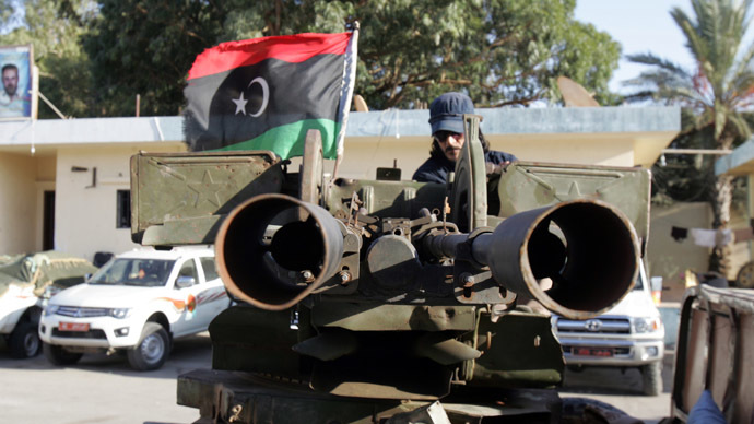 A Libyan citizen soldiers sits on an armed vehicle flying their national flag in the coastal city of Benghazi (AFP Photo)