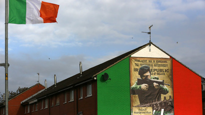 An Irish flag flies beside a mural in the Ardoyne area of North Belfast displaying an image of a I.R.A. gunman November 5, 2013. (Reuters/Cathal McNaughton)