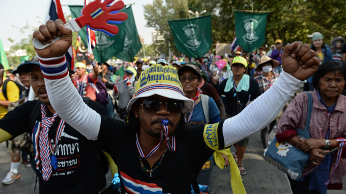 Thai anti-government protesters wave clappers as they march through the streets of Bangkok on January 9, 2014 (AFP Photo / Christophe Archambault)