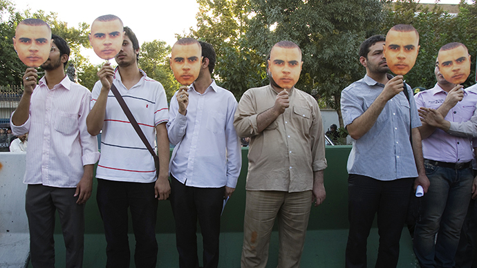Iranian men hold masks bearing the likeness of 29 year old Afro-Caribbean, Mark Duggan who died from a gunshot wound after an incident involving armed police in London, during a protest in front of the British embassy in central Tehran August 14, 2011. (Reuters / Morteza Nikoubazl)