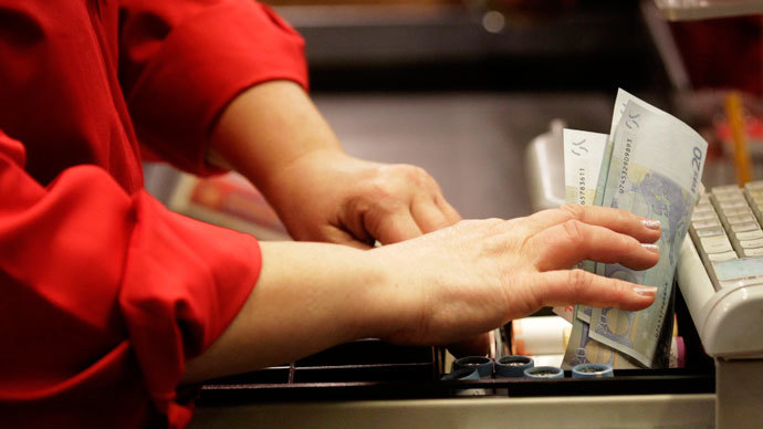 A cashier holds euro banknotes in Riga January 1, 2014.(Reuters / Ints Kalnins)