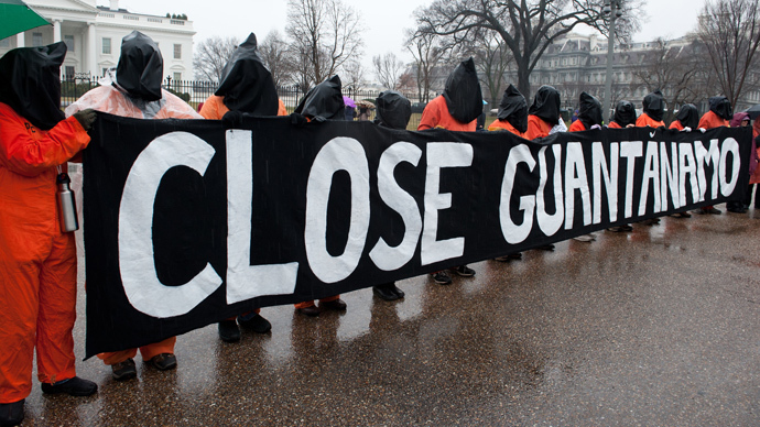 Protestors wear orange detainee jumpsuits and black hoods as they hold a banner calling for the closing of the US detention center at Guantanamo naval base in Cuba in front of the White House in Washington on January 11, 2014 to mark the 12th anniversary of the arrival of the first detainees at the controversial jail. (AFP Photo / Nicholas Kamm)