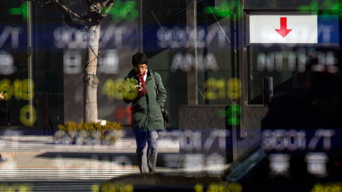 A man is reflected in a stock quotation board outside a brokerage in Tokyo January 28, 2014.(Reuters / Toru Hanai)