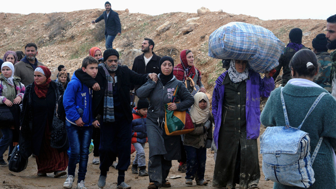 Syrian residents walk near a highway as they flee their homes following clashes between opposition fighters and forces loyal to Syria's President Bashar al-Assad in the Adra area, east of Damascus in this handout photograph released by Syria's national news agency SANA. (Reuters / SANA / Handout via Reuters)