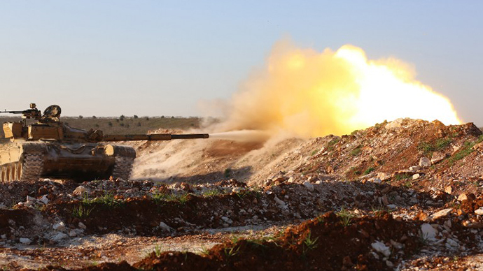 A tank confiscated by rebel fighters fires at a pro-government position near the Syrian city of Hama, on February 19, 2014. (AFP Photo / Abu Hadi Al-Hamwi)