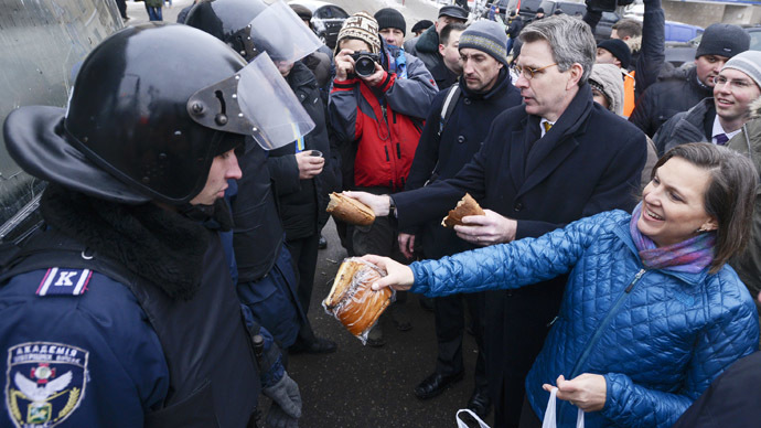 A handout picture released on December 10, 2013 by Ukrainian Union Opposition press services shows US Assistant secretary of State for European and Eurasian Affairs Victoria Nuland (R) distributing cakes to riot policemen on the Independence Square in Kiev on December 10, 2013. (AFP Photo)