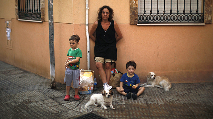 Gonzalez and her children stand in a street with their dogs and belongings after Spanish riot police evicted them from an unoccupied building of flats in Malaga (Reuters /  Jon Nazca)