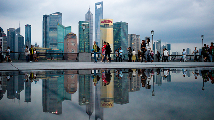Pedestrians walk past the skyline of the city's financial district in Shanghai (AFP Photo / Philippe Lopez)
