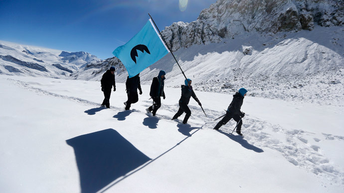 "Greenpeace activists walk as they hold a flag on Olivares glacier for the symbolic founding of ""Republica Glaciar"" (Glacier Republic), some 5,000 meters (16,404 ft.) above sea level, at Los Andes Mountain range, near Santiago city, March 2, 2014.(Reuters / Ivan Alvarado )"