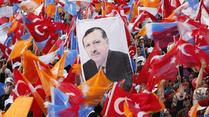 Supporters hold up a portrait of Turkey's Prime Minister Tayyip Erdogan while waving Turkish and AK Party (AKP) flags during an election rally in Istanbul March 23, 2014. (Reuters)