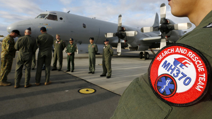 South Korea's Navy Lieutenant Commander Oh Kang-min (R) is pictured wearing a Malaysia Airlines flight MH370 search and rescue team patch on his sleeve as he waits to meet Australia's Prime Minister Tony Abbott in front of a Royal Australian Air Force AP-3C Orion aircraft at RAAF Base Pearce near Perth March 31, 2014. (Reuters)