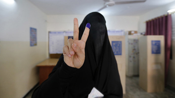 A fully-veiled woman shows her ink-stained finger at a polling station during voting for Iraqi parliamentary election in Baghdad April 30, 2014. (Reuters)