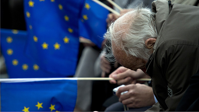 An elderly man slouches as other supporters hold EU flags during a campaign rally for the Christian Democratic Union (CDU) attended by the German chancellor ahead of European Parliament elections due to take place on May 25, 2014 (AFP Photo / John Macdougall)