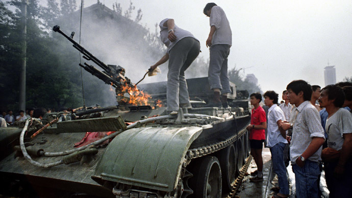 (FILES) In a file picture taken on June 4, 1989 Chinese residents check a burning armoured personnel carrier which was set on fire during clashes near Tiananmen Square in Beijing. (AFP Photo / Files / Tommy Cheng)