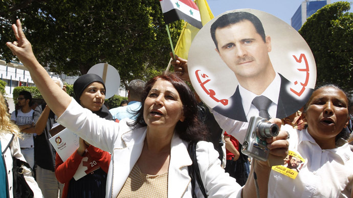 A woman together with others, including Syrians living in Tunisia, holds a placard of Syria's President Bashar al-Assad, in Tunis June 3, 2014. (Reuters)