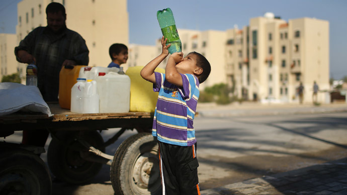 A Palestinian boy drinks water next to a cart loaded with containers filled with water from public taps in the northern Gaza Strip (Reuters/Mohammed Salem)